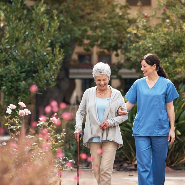 Une aide soignante et une personne âgé se promenade