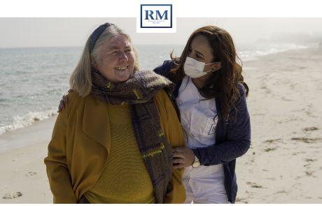 Une aide soignante et une personne âgé qui rient